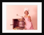 1960s Woman Wearing Pink Party Dress And Chef Hat Grilling Hot Dogs Drinking Beer by Corbis