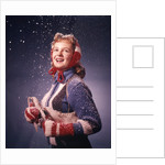 1960s Young Woman Wearing Red Mittens Ear Muffs Blue Sweater Holding Ice Skates In Falling Snow by Corbis