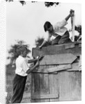 1930s Pair Of Boys Building Shack One Nailing Board To Side One On Roof With Saw by Corbis