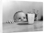 1950s Toddler Reaching Up To Table To Grab Milk Glass by Corbis