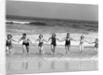 1930s Group 7 People Holding Hands Running Out Of Surf Onto Beach by Corbis