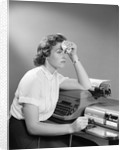 1950s Ailing Secretary Sitting At Desk With Typewriter And Dictation Machine Holding Handkerchief To Forehead by Corbis