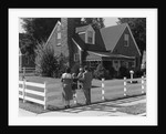 1950s Family Standing By White Fence Looking At Brick House by Corbis