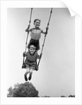1930s Two Boys Sitting Standing On Playground Swing by Corbis