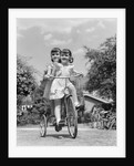 1940s Twin Girls Riding Outside On Tricycle by Corbis