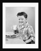 1930s 1940s Freckle-Faced Boy Sitting Dinner Table Holding Glass Milk by Corbis