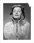 1950s Woman Wearing Peignoir With Eyes Closed Hands Held Near Face Ecstatic Facial Expression by Corbis