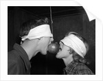 1950s Blindfolded Couple Trying To Eat An Apple Hanging In Air From A String Inside by Corbis