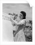 1940s Woman Hanging Laundry On Clothesline Outdoors by Corbis