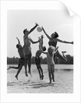 1960s Family Jumping Playing Beach Volleyball by Corbis