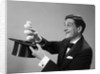 1960s Profile Magician Man Pulling 4 Eggs Out Of Hat Holding Them Between Fingers by Corbis