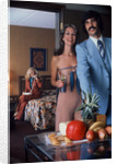 1970s Couple Welcoming Guest To Party At Home Woman Using Phone In Another Room by Corbis