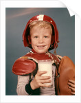 1960s Boy Wearing Red Helmet Football Shoulder Pads Holding Glass Milk and Football by Corbis