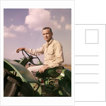 1960s Portrait Man Farmer Sitting On Green Tractor Smoking Cigarette by Corbis
