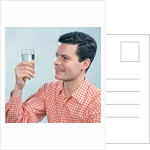 1960s Profile Man Wearing Red Checkered Shirt Holding Glass Of Water by Corbis