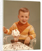 Boy Sitting At Ice Cream Parlor Table Eating Whipped Cream Cherry Topped Sundae+ by Corbis