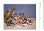 1960s Family On Sunny Beach Under Umbrella With Picnic Basket by Corbis