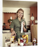 1960s Young Housewife While Checking Grocery Shopping Receipt In Kitchen by Corbis