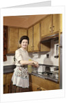 1960s Woman Housewife Wearing An Apron Stirring Cooking Pot At Kitchen Stove by Corbis