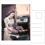 1950s Housewife Wearing Apron And Oven Mitts Taking Roast Beef With Potatoes Out Of Kitchen Oven by Corbis