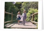 1960s Little Boy And Girl Holding Hands And Walking Across Wooden Footbridge by Corbis