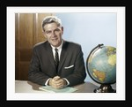 1960s Portrait Man Businessman Sitting At Desk Next To Globe Of The Earth by Corbis