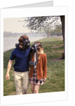 1970s Young Romantic Teenage Couple Man Woman Wearing Gas Masks Walking By River by Corbis