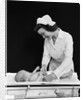 1940s Woman Nurse Changing Baby Diaper In Nursery by Corbis