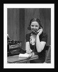 1930s Woman Receptionist Secretary Sitting At Desk In Office Talking On Telephone by Corbis