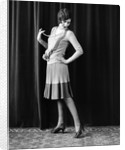 1920s Flapper Woman Posing Hand On Hip Holding String Of Pearls Stretching Leg Checking Hosiery Seams by Corbis