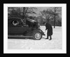 Woman Passenger Watching Man Motorist Try To Crank Start A Chevrolet Coupe Stalled In Snow by Corbis