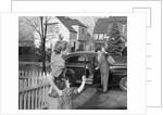 1950s Mother And Daughter Waving To Father Opening Automobile Door In Front Of Suburban Home by Corbis
