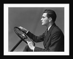 1930s 1940s Man Wearing Suit And Tie Holding Automobile Steering Wheel by Corbis