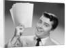 1950s Young Businessman Holding Up Handful Of Papers by Corbis