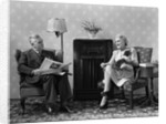 1940s Senior Couple Sitting In Living Room Reading Newspaper And Magazine Listening To Radio by Corbis