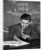 1920s 1930s Boy At Desk In Classroom In Front Of Blackboard Shooting Paper Wad With Rubber Band by Corbis