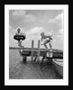 1940s 1950s Two Boys Wearing Inflatable Inner Tubes About To Jump In Lake Off Pier by Corbis