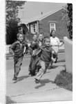 1950s School Children Running Around Corner Of Picket Fence In Suburban Neighborhood by Corbis