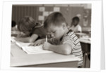 1960s Boy Striped T-Shirt Elementary School Classroom Sitting Desk Writing Test by Corbis