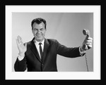 1960s Businessman Holding Telephone At Arms Length With Expression Of Disgust Or Rejection by Corbis