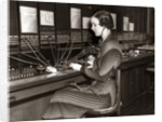 1930s Woman Telephone Operator Sitting At Large Manual Switchboard Directing Calls by Corbis