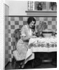 1920s Woman Sitting At Kitchen Table With Table Cloth While On Phone by Corbis
