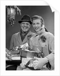 1950s Husband And Wife Carrying Armload Of Christmas Packages Standing In Snow Under Porch Light by Corbis