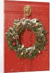 Christmas wreath hanging on a door by Corbis