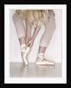 Ballerina adjusting toe shoe by Corbis