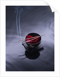 Burning incense on top of bowl of petals by Corbis