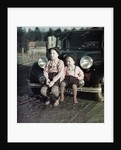 Two brothers sit on the bumper of the family Mercedes Benz in Germany, ca. 1949 by Corbis