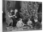 Family christmas photo father two daughters and son with presents and tree by Corbis