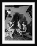 3 boy scouts sitting tent night telling ghost stories by Corbis