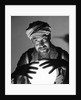 Scary fortune teller man with hands on lighted crystal ball wearing turban by Corbis